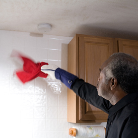 Graphic showing a man dusting a wall below a smoke alarm