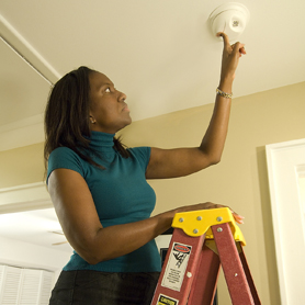 Graphic showing a woman installing a battery in a smoke alarm