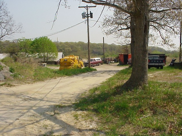 image 46a - a dirt road leads to a building with trucks and heavy duty work vehicles