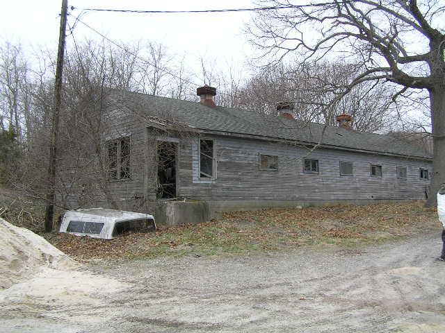 image 46b - an abandoned house, its door is off. a truck bed cap lay on the ground next to the house